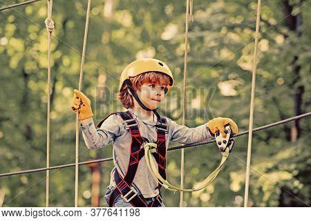 Adventure Climbing High Wire Park. Cute School Child Boy Enjoying A Sunny Day In A Climbing Adventur