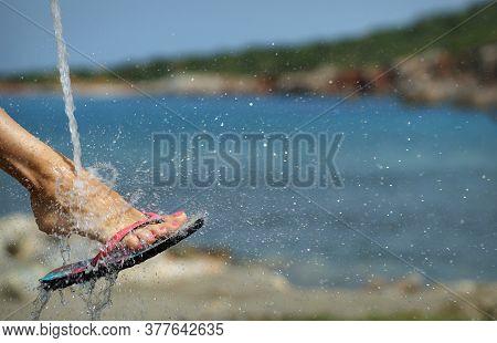 Foot In Beach Slides Under Water Spray, Water Drops Splashing Around. Blue Sea And Coastline. Free S