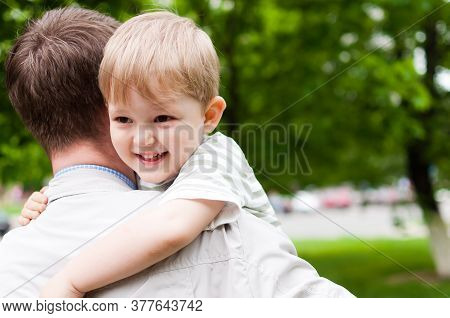 Portrait Of Cute Little Boy Held In Father's Arms. Happy Loving Family. Cute Baby And Daddy. Concept