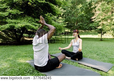 Morning Yoga Exercises And Healthy Lifestyle. Multiethnic Couple Doing Yoga In Park Together, Sittin