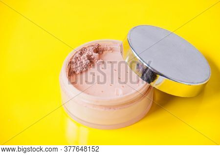 Open Jar With Loose Powder On A Yellow Background