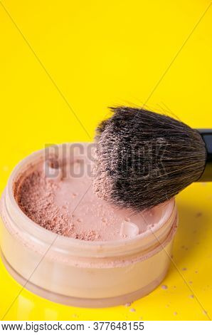An Open Jar Of Loose Powder And A Large Cosmetic Brush On A Yellow Background