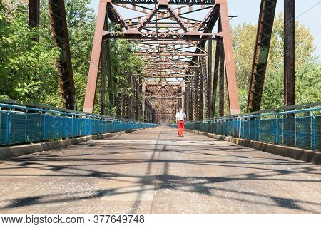 St Louis Usa - September 3 2015; Structural Truss Casts Shadows On Platform Of Bridge As Man In Red