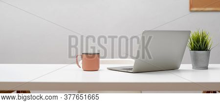 Home Office Desk With Laptop, Mug, Plant Pot And Copy Space On White Table With White Chair