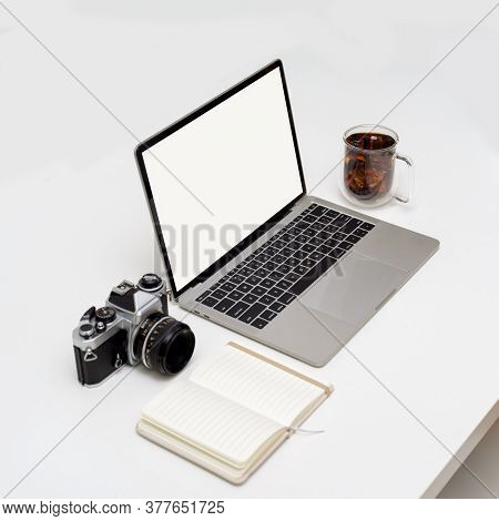 Blank Screen Laptop On White Table With Opened Notebook, Camera And Coffee Cup