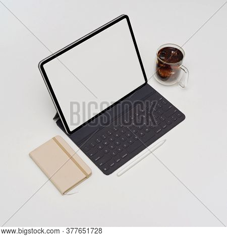 Blank Screen Tablet With Keyboard On White Table With Diary Book And Coffee Cup
