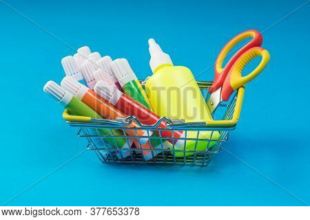 A Bottle Of Glue, Scissors And Markers In An Iron Basket On A Blue Background. Universal Markers For