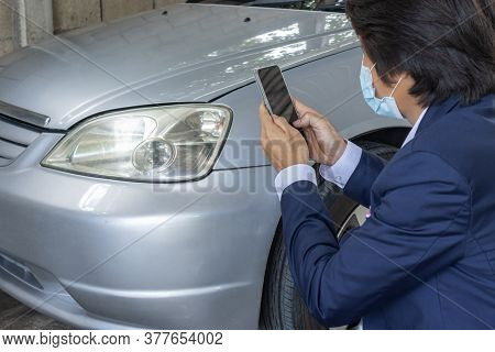 Asian Insurance Agent Or Insurance Agency In Suit Wear Mask Take Car Crash Photo And Inspecting Car