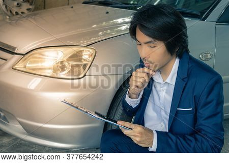 Asian Insurance Agent Or Insurance Agency In Suit Reading Data Report And See Smartphone Of Car Cras