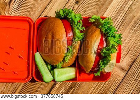 Hamburgers With Lettuce In Lunchbox On Rustic Wooden Table. Top View