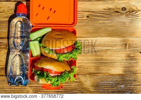 Hamburgers With Lettuce In Lunchbox And Bottle Of Water On Rustic Wooden Table. Top View