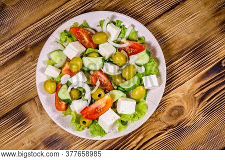 Ceramic Plate With Greek Salad On Rustic Wooden Table. Top View