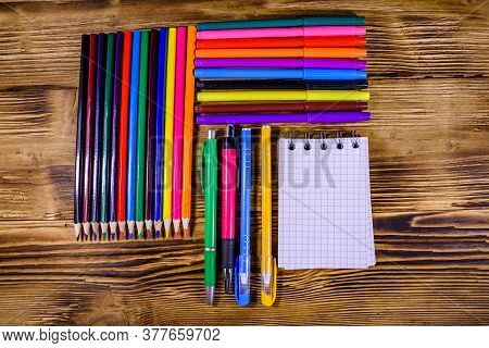 Different School Stationeries (pens, Notepad, Pencils, Felt Tip Pens And Ruler) On Wooden Background