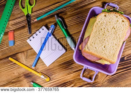 Different Stationeries And Lunch Box With Sandwiches On Wooden Table. Top View