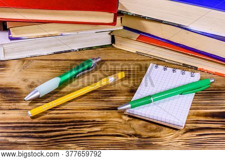 Opened Small Notepad And Ball Pens On A Wooden Table In Front Of Stack Of Books