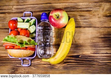 Ripe Apple, Banana, Bottle Of Water And Lunch Box With Hamburger, Cucumbers And Tomatoes On Rustic W