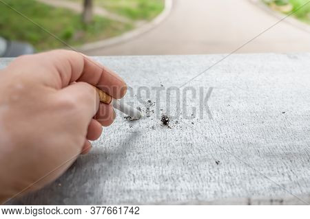 The Hand Of A Smoking Person Puts Out A Cigarette Butt On The Window Sill Of A Home Window With A Vi