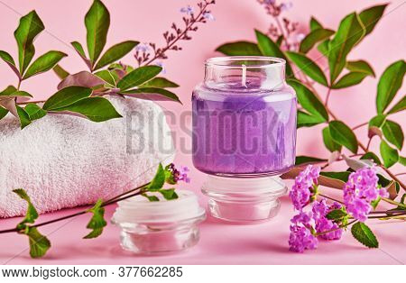 Scented Candle For Spa And Home With Lavender Scent And Green Leaves On A Pink Background.
