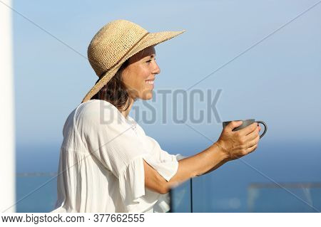 Side View Portrait Of A Happy Adult Woman With Pamela Contemplating Views With Coffee In A Balcony O