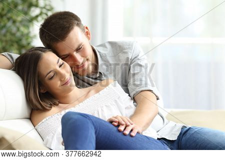 Happy Couple In Love Cuddling Holding Hands Sitting In The Sofa In The Living Room At Home