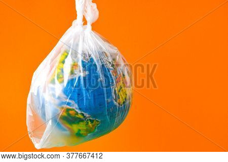 Ball In The Form Of A Globe Is In A Plastic Bag. Concept Of Plastic Pollution Of The Earth. World En