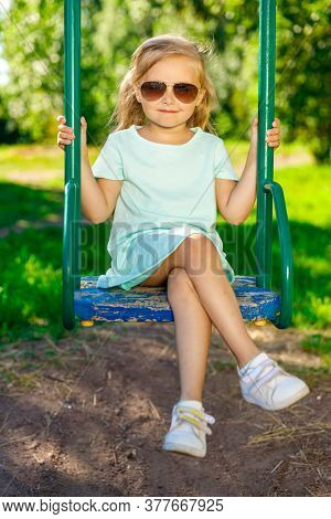 Beautiful Girl In A Blue Dress And Sunglasses Swinging On A Swing