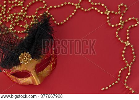 Christmas Red Background With Masquerade Mask And Golden Beads. Flat Lay Style. New Year Masquerade