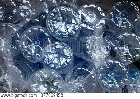 Many Used Plastic Bottles Pile Background. Clear Empty Water Containers Piled At A Garbage Recycling