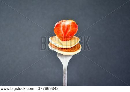 Selective Focus On Fork With Tiny Pancakes And Strawberry. Pancake Porridge, Mini Pancakes Cereal In