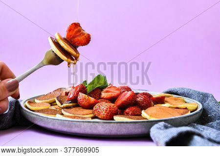 Selective Focus On Maple Syrup Pouring On Fork With Tiny Pancakes And Strawberry. Pancake Porridge,