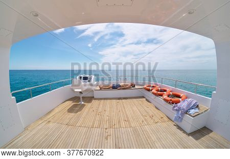 Man relax on yacht. Pleasure recreation at sea. View from yacht flybridge open deck, modern and luxury equipped with navigation dashboard. Lifestyle freedom concept.