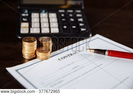 Signing A Contract, Points And Coins Next To The Calculator