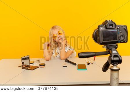 Little Girl Blogger In The Yellow Studio In Front Of Camera Making Video. Working As Blogger, Record