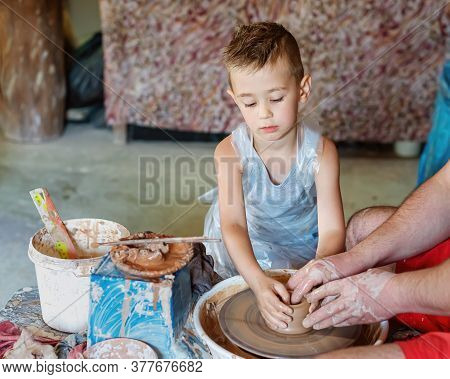 Potter Teaches A Little Kid How Make Clay Pot. Hands Working On Pottery Wheel.