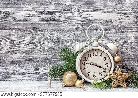 Christmas Background With Alarm Clock, Branches Of Fir Tree And Gold Decorations. Space For Text. Ch