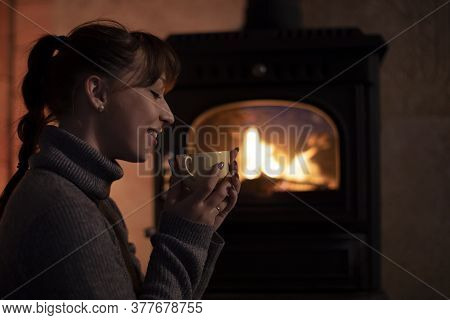 Portrait Of Young Girl In A Warm Sweater Drinking Hot Drink From Mug By The Fireplace. Cozy Home Chr