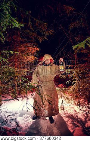 Medieval Monk In Canvas Sackcloth Robe With Lattern In Dark Forest With Snow And Red Light On Winter