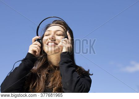 Happy Woman With Beautiful Smile Puts On Headphones Listen Positive Music With Closed Eyes, Blue Sky
