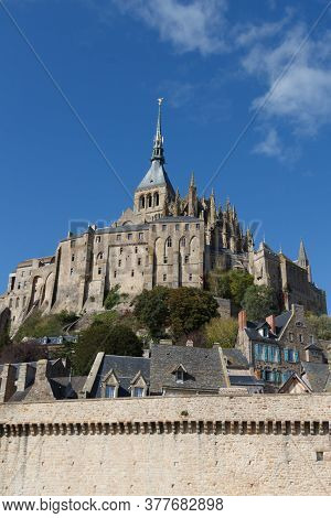 Abbey And Ramparts Of Mont Saint-michel Against Blue Sky
