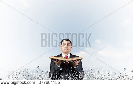 Senior Businessman Holding Old Open Book. Man In Business Suit And Tie Standing On Cityscape Backgro