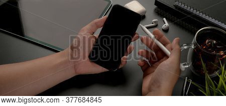 Overhead Shot Of Male Hands Using Smartphone While Sitting At Dark Worktable