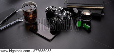 Dark Office Desk With Smartphone, Camera, Supplies And A Cup Of Beverage