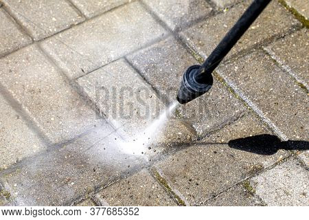 Sprayer Of High-pressure Washer Cleans Concrete Stones Of Garden Line. Spring Cleaning Concept. Natu