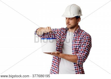 Caucasian Handyman Worker In Plaid Shirt And Hard Hat Holding Paint Bucket. Builder Or Painter Decor
