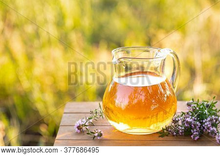 Thyme Essential Oil In A Glass Jug And Branches Of A Fresh Thyme Plant With Flowers On A Wooden Back