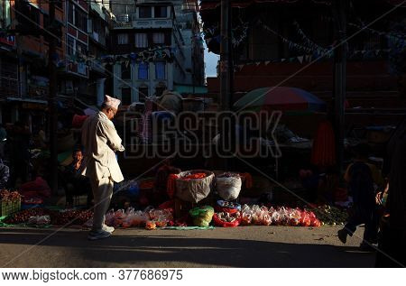 Kathmandu, Nepal - June 20, 2019: Sun shining on nepali man in traditional clothes on narrow shopping street in old town, Local daily life