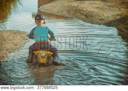 Back View Of Anonymous Boy Driving Toy Transport In Dirty Brook While Playing In Countryside.