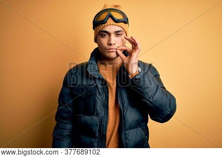 Young brazilian skier man wearing snow sportswear and ski goggles over yellow background mouth and lips shut as zip with fingers. Secret and silent, taboo talking