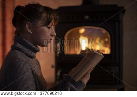 Portrait Of Young Girl In A Warm Sweater Reading A Book At Home By The Fireplace. Cozy Home Christma