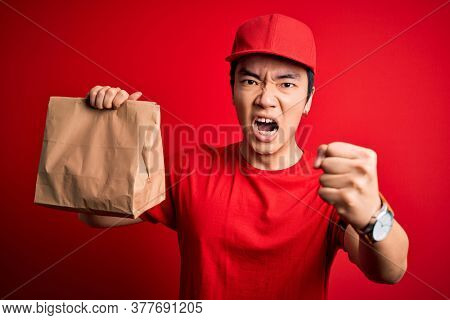 Young handsome chinese delivery man holding takeaway paper bag with food annoyed and frustrated shouting with anger, crazy and yelling with raised hand, anger concept